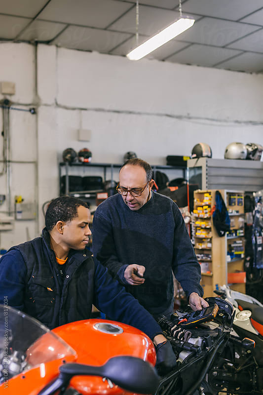 Mechanical Operators in a Motorbike Workshop by Victor Torres for Stocksy United