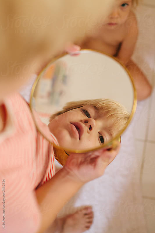 Interesting, quirky image of a boy looking in a circular mirror.  by Julia Forsman for Stocksy United
