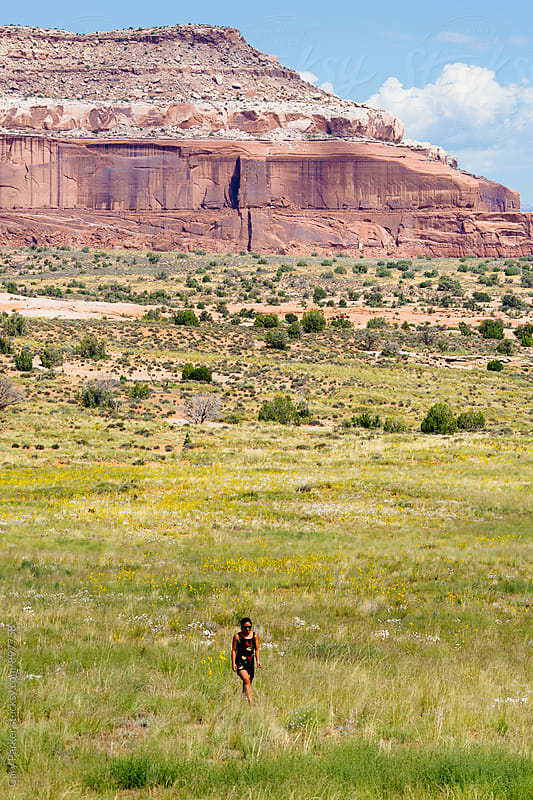 A girl walking in a grassy field with rock formation in the background by Gary Parker for Stocksy United