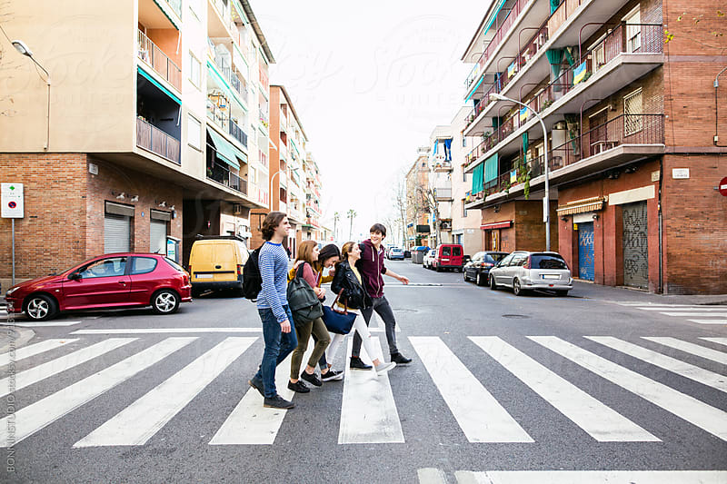Side view of group of teen friends crossing the street. by BONNINSTUDIO for Stocksy United