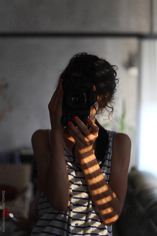 Female photographer taking a photo of herself in the mirror by Marija Mandic for Stocksy United