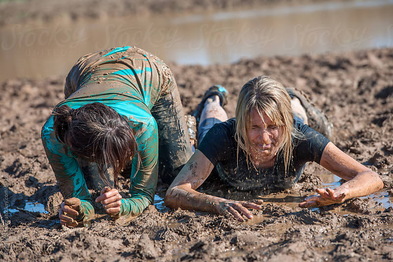 Woman Check's as Her Teammate Spews Muddy Water by Brian McEntire for Stocksy United