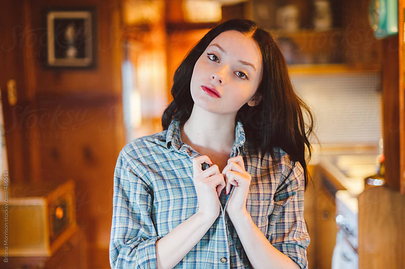 Young Woman in a Vintage Trailer Wearing A Blue Plaid Shirt by Briana Morrison for Stocksy United