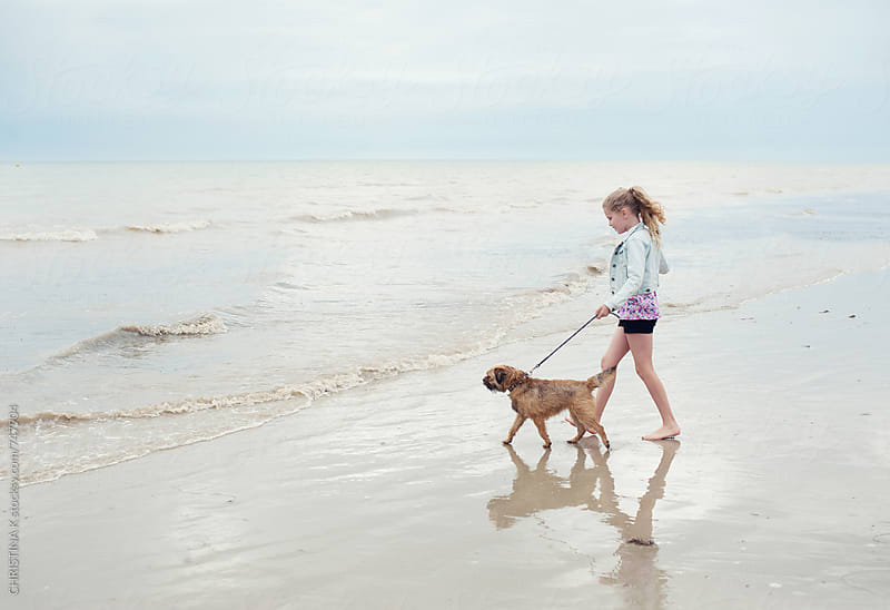 Girl and her dog walking towards the sea by CHRISTINA K for Stocksy United