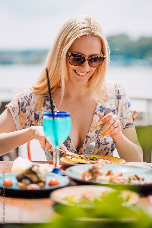 Woman having a lunch in the restaurant on the sunny day  by Boris Jovanovic for Stocksy United