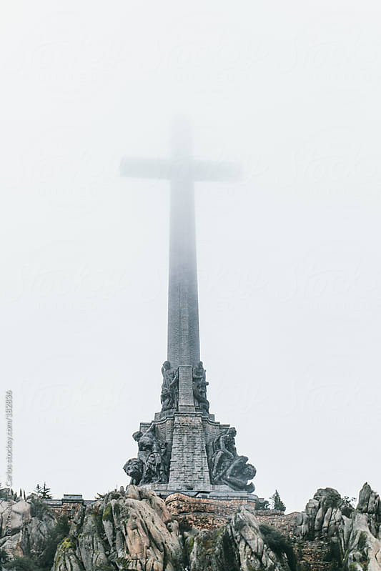 Conmemorative christian cross monument covered by fog in Valle de Los Caidos, Madrid, Spain by Alejandro Moreno de Carlos for Stocksy United