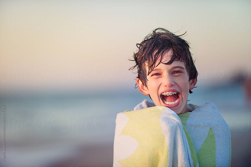 Boy with a big toothy smile and braces by Angela Lumsden for Stocksy United