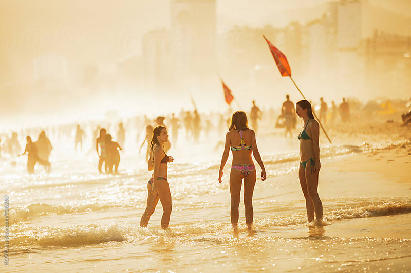 Three friends walking in the surf on Ipanema Beach by HOWL for Stocksy United