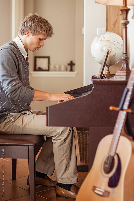Teenager Playing Piano at Home by Geoffrey Hammond for Stocksy United