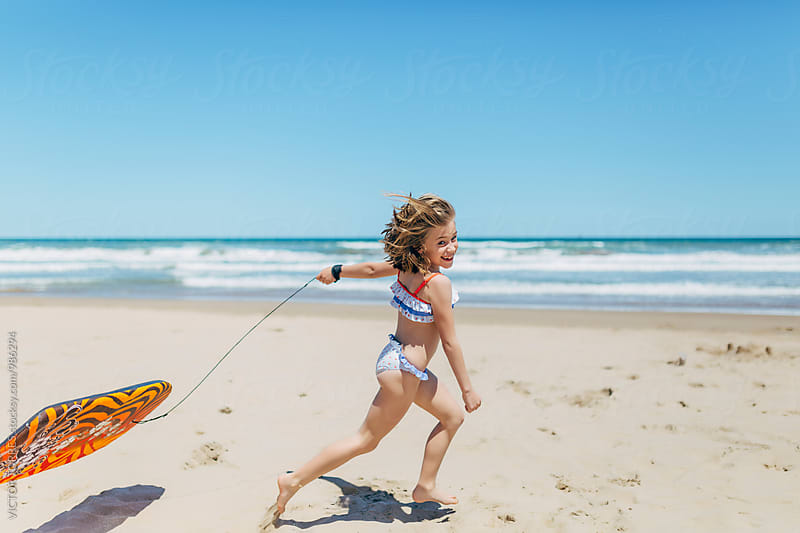 Little Cute Girl Running at Beach with a Bodyboard by Victor Torres for Stocksy United