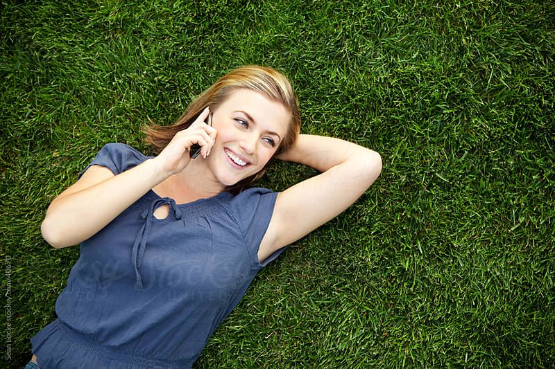 Grass: Woman Talking on Cell Phone  by Sean Locke for Stocksy United