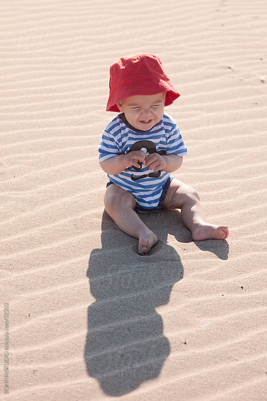 Baby smiling sitting on the sand of the beach. by BONNINSTUDIO for Stocksy United