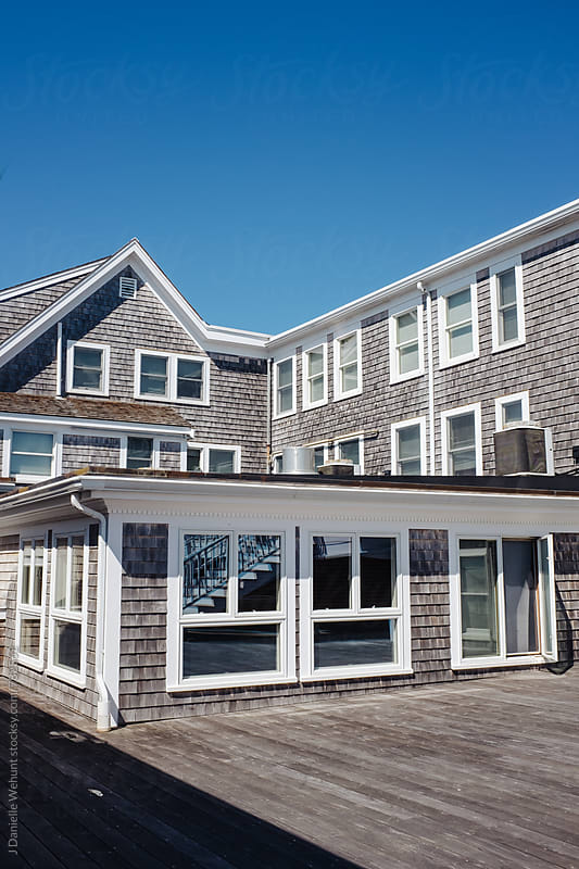 The exterior view of a grey shingle siding building. by J Danielle Wehunt for Stocksy United
