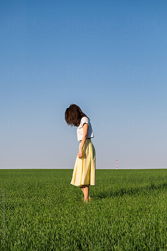 Side view of brunette in yellow skirt on grass by T-REX & Flower for Stocksy United