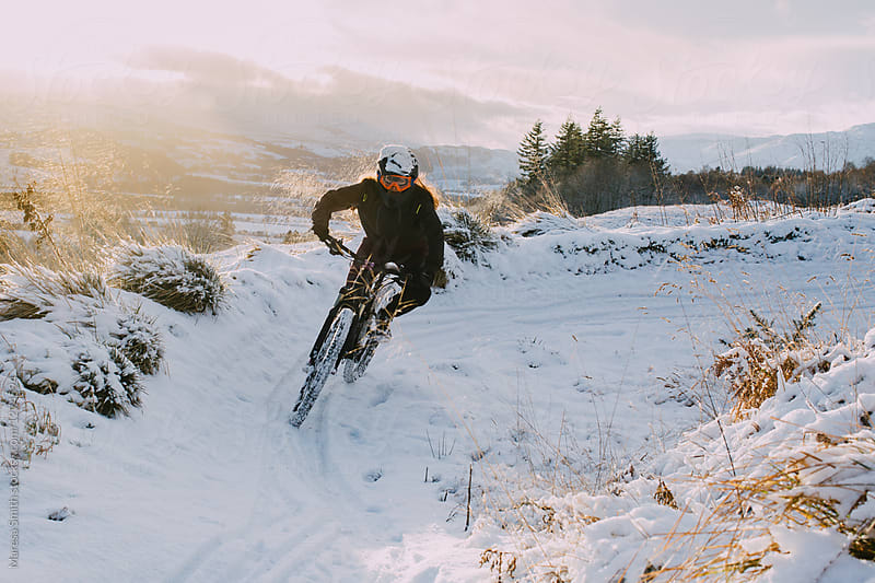 A female mountain biker wearing goggles riding a snow-covered track