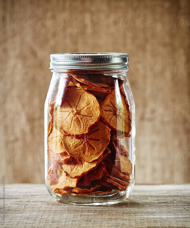 Preserved fruit persimmons in glass mason jar by Trinette Reed for Stocksy United