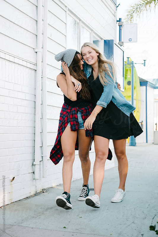 Two female friends walking down the sidewalk and having fun by Emmanuel Hidalgo for Stocksy United