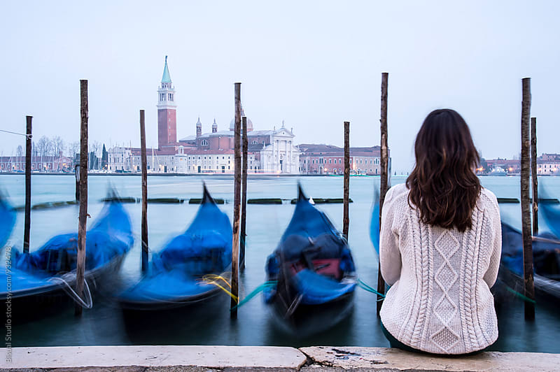 Woman sitting in front of some gondolas in Venice by Bisual Studio for Stocksy United