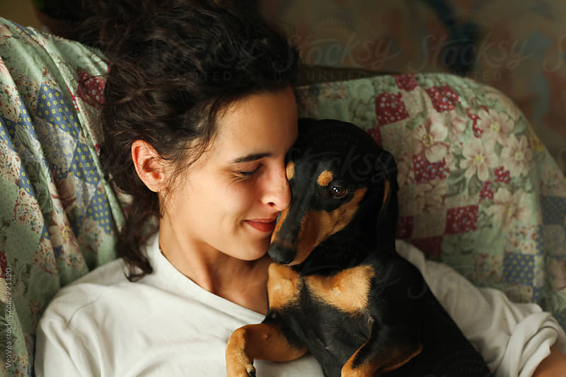 Young woman hugging her small black dog on the couch  by VeaVea for Stocksy United