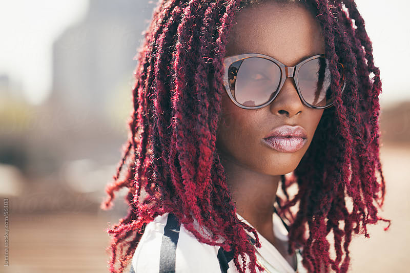 African Woman With Sunglasses and Pink Dreadlocks by Lumina for Stocksy United