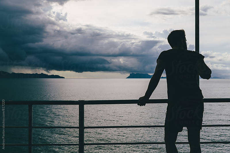 Man standing on ferry deck and looking away by Andrey Pavlov for Stocksy United