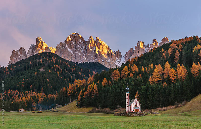 panorama shot of the St Johann Church in Ranui in Villnoss, Val di funes, with the Geisler Mountain group in the back by Leander Nardin for Stocksy United