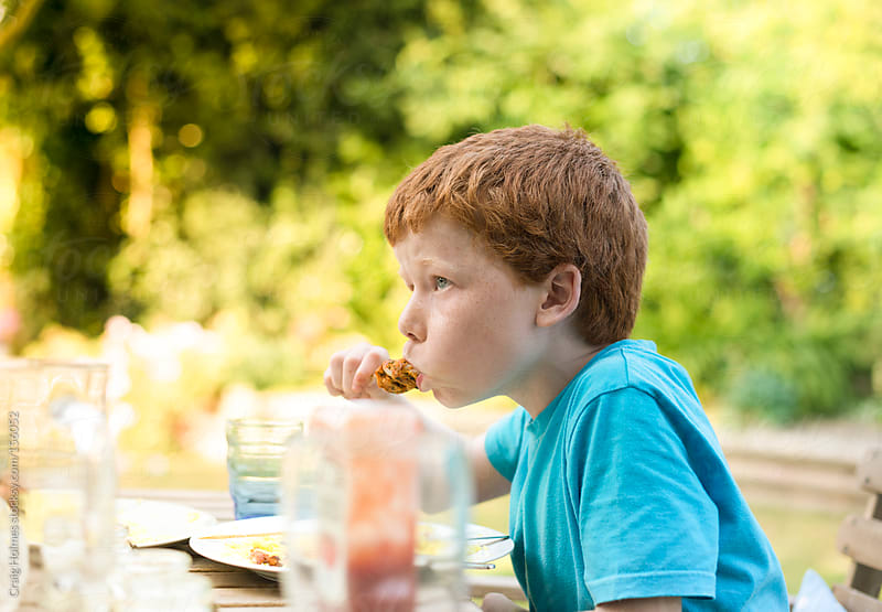 A boy eating a meal in the garden in summer by Craig Holmes for Stocksy United
