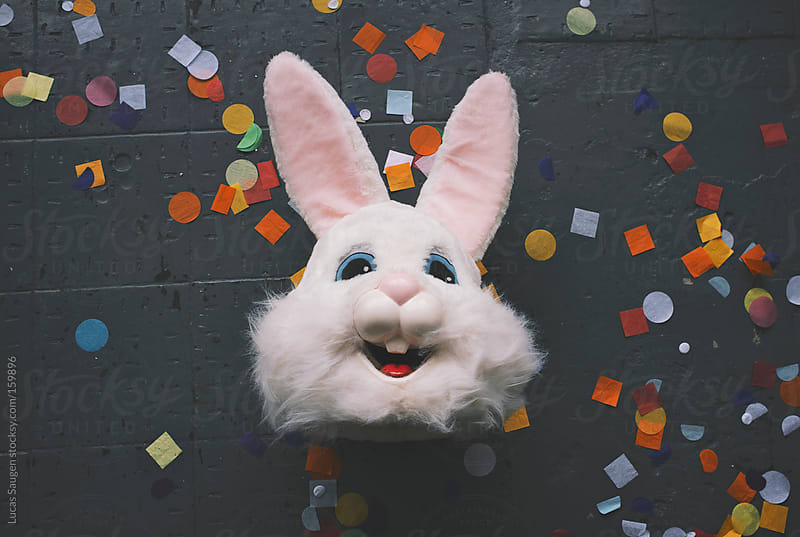Head to a rabbit costume laying on a concrete floor with colorful confetti. by Lucas Saugen for Stocksy United