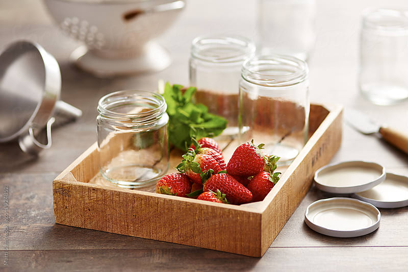 Glass cans and strawberries in wooden tray by Martí Sans for Stocksy United