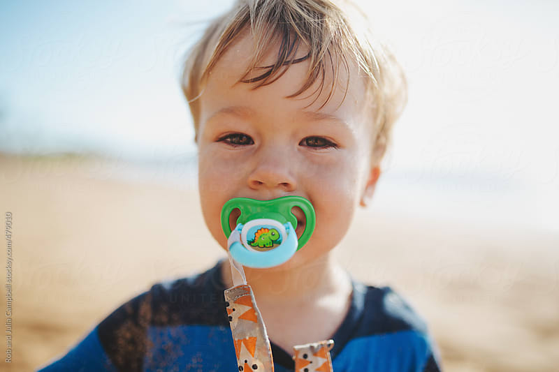 Cute toddler boy with soother on beach in summer by Rob and Julia Campbell for Stocksy United