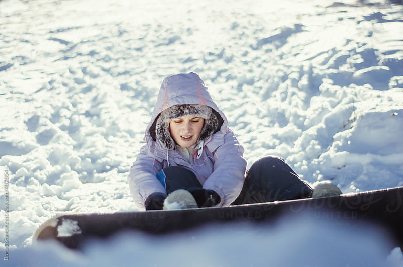 Snowboarder shifting her board by Boris Jovanovic for Stocksy United