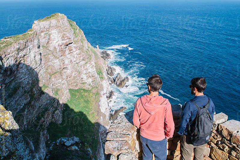 Two young men friends looking to the coast from a lookout. Cape of Good Hope, South Africa by Alejandro Moreno de Carlos for Stocksy United