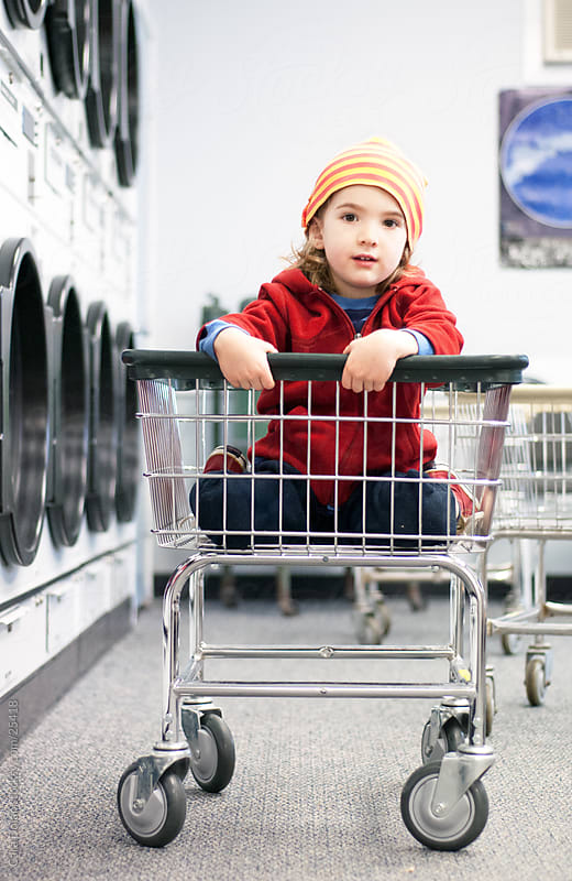 Boy hangs out in cart at a laundromat by Cara Slifka for Stocksy United