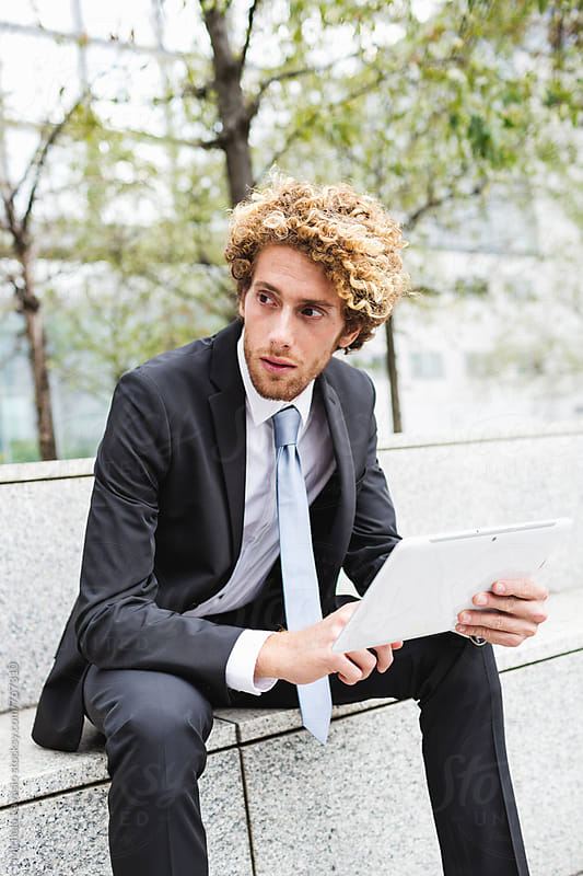 Young businessman holding his digital tablet outdoors by michela ravasio for Stocksy United