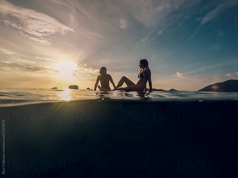 Young beautiful couple enjoying the sunset over the floating platform of bamboo in the sea by Blue Collectors for Stocksy United