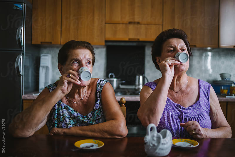 Two seniors women drinking coffee by GIC for Stocksy United