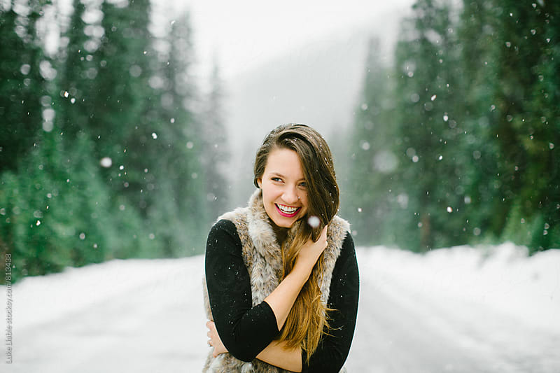 Young attractive girl embracing the snow in winter by Luke Liable for Stocksy United