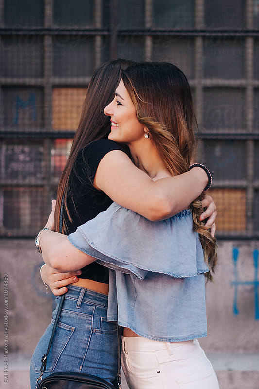 Mother and daughter hug each other on the street  by Evil Pixels  Photography for Stocksy United