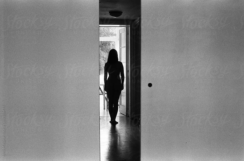A black and white film photo of silhouette of a young beautiful woman by Anna Malgina for Stocksy United