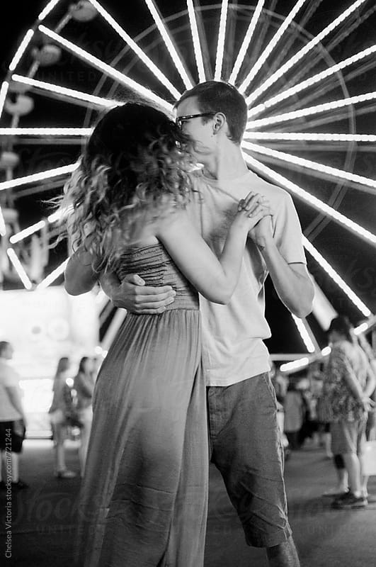 A young couple in front of a ferris wheel by Chelsea Victoria for Stocksy United