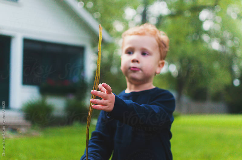 A child plays with a stick  by Chelsea Victoria for Stocksy United