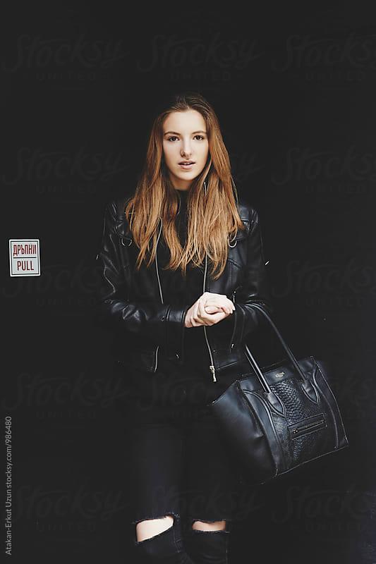 Ginger female model posing against black wall by Atakan-Erkut Uzun for Stocksy United