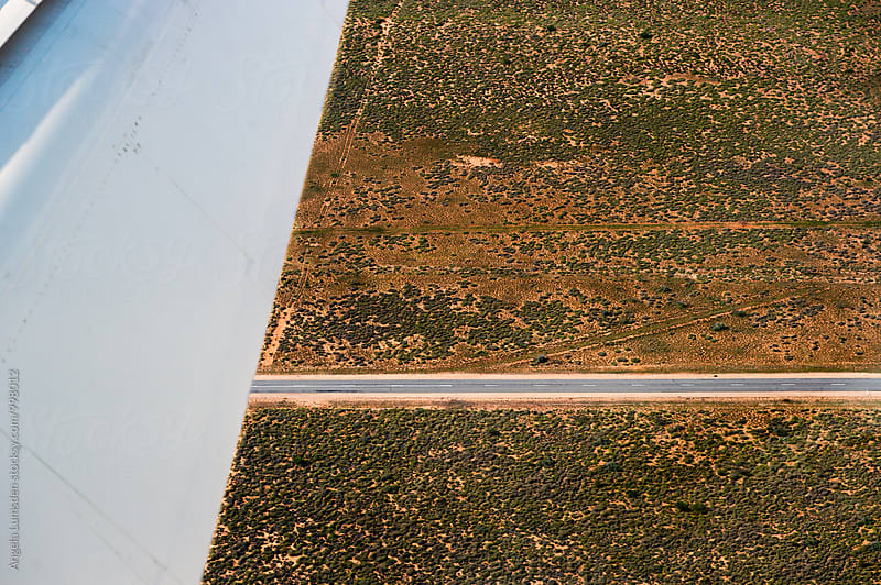 Aerial view of scrub and a desert road in Western Australia by Angela Lumsden for Stocksy United