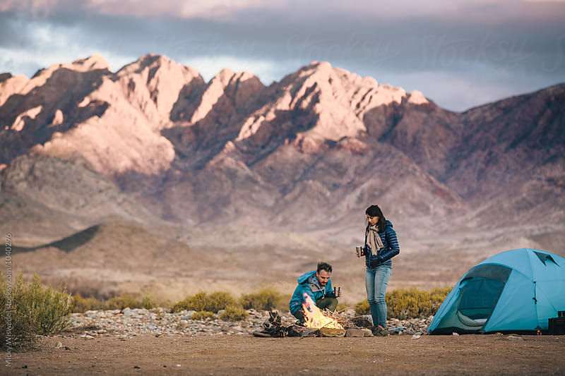 Hiking couple at their camp fire amongst rugged desert mountains by Micky Wiswedel for Stocksy United