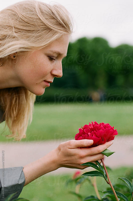 Young woman touches a peony by Liubov Burakova for Stocksy United