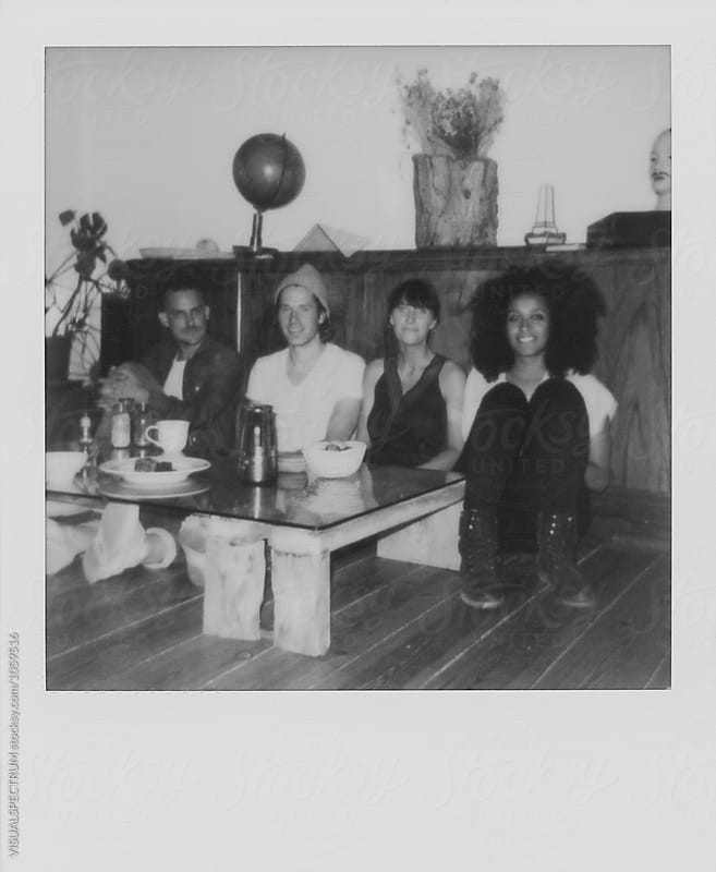 Black and White Polaroid of Four Young Friends Sitting on Floor in Cool Living Room by VISUALSPECTRUM for Stocksy United