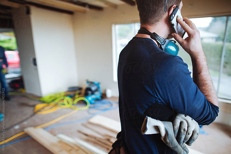 Man talking on cell phone on home renovation jobsite by Rob and Julia Campbell for Stocksy United