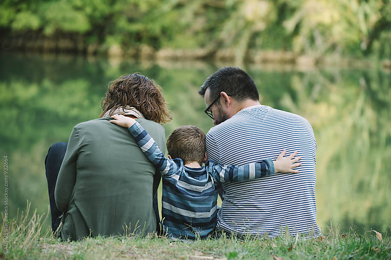 Son embracing parents by the river by Blai Baules for Stocksy United