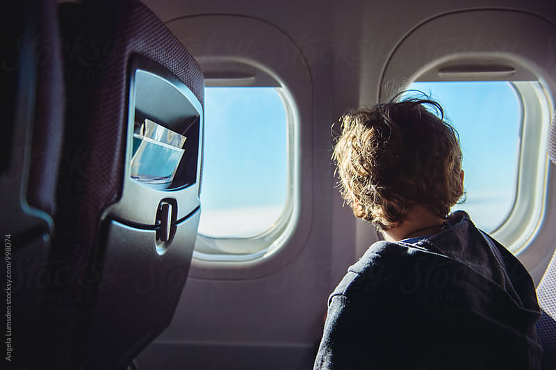 Boy looking out an airplane window by Angela Lumsden for Stocksy United