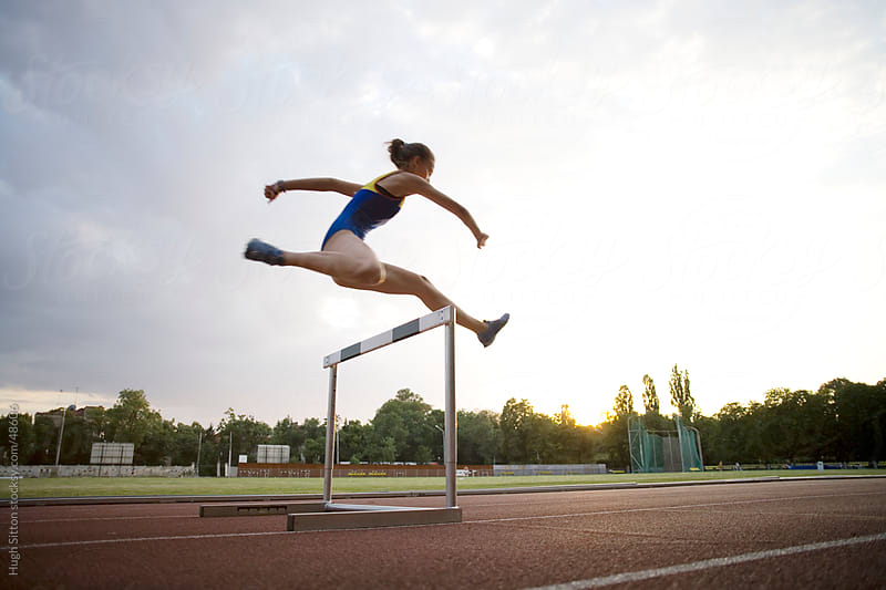Young female hurdler training at dusk. by Hugh Sitton for Stocksy United